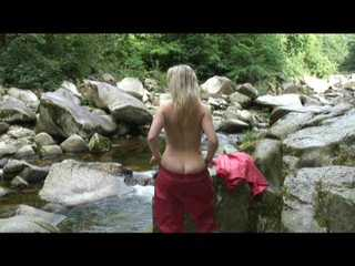 Watching Sophie wearing only a red shiny nylon rainpants and rain jacket taking a bath in a river (Video)