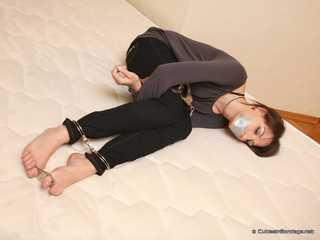 Satisfaction Girl - Barefoot brunette beauty uses cuffs and tape gag