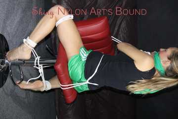 Watching sexy Sandra wearing a sexy green shiny nylon shorts and a black top being tied and gagged with ropes and a clothgag on a chair (Pics)