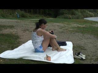 Enni wearing shiny nylon shorts and a rain jacket as well as a rain pants over the shorts (Video)