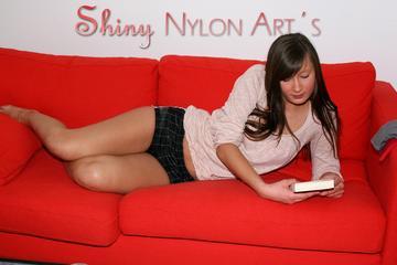 Alina lolling on a sofa wearing a sexy black shiny nylon shorts and a white top (Pics)