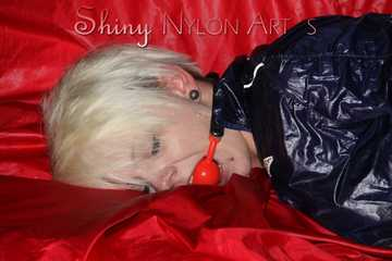 Sexy Courtney being tied and gagged with ropes and a ballgag on a bed wearing dark blue rainwear (Pics)
