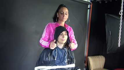 Sexy Ajyana being tied, gagged, hooded and dominated by Stella wearing sexy shiny nylon rainwear on a hairdresser´s chair Part 1 of 2 (Video)