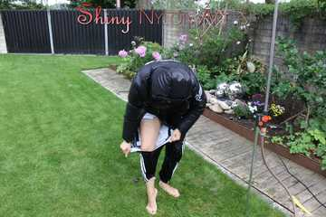 Watching sexy Aiyana wearing a supersexy black shiny nylon rainpants and a black down jacket playing with water of the garden shower and destroying her pant (Pics)
