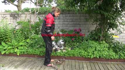 Watching sexy Sandra wearing sexy shiny nylon rainwear gardening outside (Video)