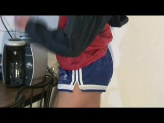 Alina sitting in front of the PC, on a sofa and ind the kitchen wearing different kind of sexy shiny nylon shorts and rain jackets (Video)
