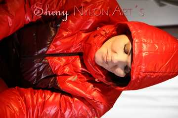 Watching sexy Jill wearing a red shiny nylon rain pants and an oldschool rain jacket under a red downjacket being tied and gagged with ropes and a ballgag on a bed (Pics)