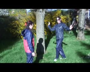Jill and a friend of her playing with eachother in the garden while wearing shiny nylon rainwear (Video)