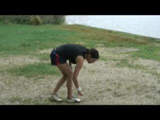 Enni wearing sexy shiny nylon shorts and top while throwing stones in a lake (Video)