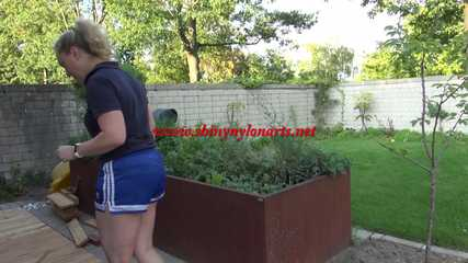 Watching Sophie wearing a blue shiny nylon shorts and a tshirt during her gardening (Video)