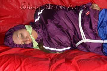 SANDRA being tied and gagged on a sofa with ropes and a clothgag wearing a sexy blue shiny nylon rain pants and a purple rain jacket (Pics)